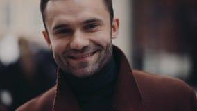 Den attraktiva affärsmannen som går ner den fullsatta gatan, kommer rakt till kameran och ger ett ljust leende Manlig skönhet stock video