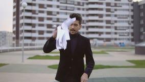 Den attraktiva affärsmannen som går och, kastar ut dokument mot affärsbyggnadsbakgrund arkivfilmer