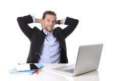 Den attraktiva affärsmannen som var lycklig på att le för arbete, kopplade av på datorskrivbordet Arkivfoton