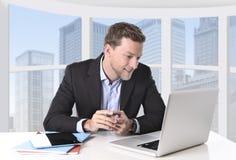 Den attraktiva affärsmannen som var lycklig på att le för arbete, kopplade av på kontoret för datoraffärsområdet Royaltyfri Fotografi