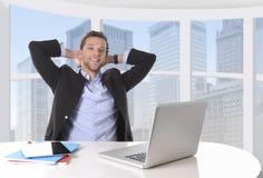 Den attraktiva affärsmannen som var lycklig på att le för arbete, kopplade av på kontoret för datoraffärsområdet