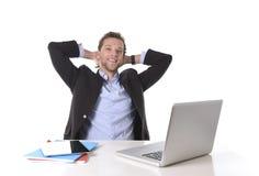 Den attraktiva affärsmannen som var lycklig på att le för arbete, kopplade av på datorskrivbordet Arkivbild