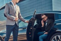Den attraktiva ansade mannen i solglasögon talar vid smartphonen och sitter i bilen, medan hans assistent är den öppnande dörren arkivbilder