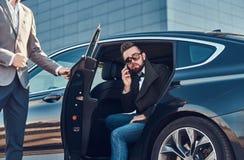 Den attraktiva ansade mannen i solglas?gon talar vid smartphonen och sitter i bilen, medan hans assistent ?r den ?ppnande d?rren fotografering för bildbyråer