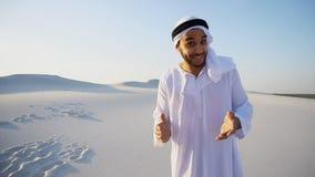 Den attraktiva arabiska manliga handboken talar om fördelar av resanden och l Arkivfoton