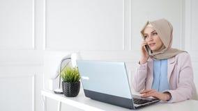 Den attraktiva avkopplade muslim kvinnan talar mobiltelefonen som sitter på hennes arbetsplats arkivfilmer