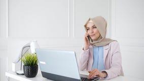 Den attraktiva avkopplade muslim kvinnan talar mobiltelefonen som sitter p? hennes arbetsplats arkivfilmer