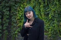 Den attraktiva blåa hårflickan som gör en gest med fingrar, kallar mig Arkivbild