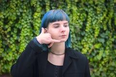 Den attraktiva blåa hårflickan som gör en gest med fingrar, kallar mig Fotografering för Bildbyråer