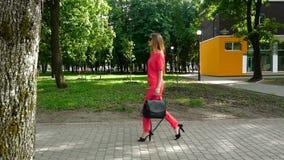 Den attraktiva blonda affärsflickan i röd dräkt går ner gatan på höga häl stock video