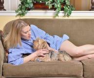 Den attraktiva blonda kvinnan lägger på soffan i mäns skjorta med hunden Arkivbild