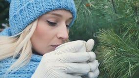 Den attraktiva blondinen dricker ett kaffe på gran-trädet bakgrunden lager videofilmer