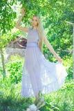 Den attraktiva blygsamma unga flickan med blont dren hår och naturligt smink i lilaklänning utomhus, mjukhet och softness på natu royaltyfri foto