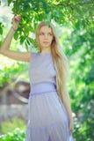 Den attraktiva blygsamma unga flickan med blont dren hår och naturligt smink i lilaklänning utomhus, mjukhet och softness på natu royaltyfri bild