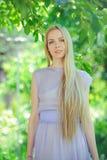 Den attraktiva blygsamma unga flickan med blont hår och det naturliga sminket i lilor klär utomhus, mjukhet och softness på natur fotografering för bildbyråer