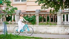 Den attraktiva brunetten i vita klänningridningblått cyklar det övergående gamla staketet som dekoreras med träd och buskar royaltyfri fotografi