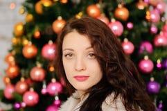 Den attraktiva brunetten med sinnliga kanter och lockigt hår poserar i studio med julgarnering som ser kameran royaltyfri foto