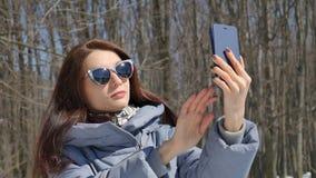 Den attraktiva brunettflickan i trendiga sunglesses som fotograferar sig som använder blå smartphonedet fria i, parkerar på stock video