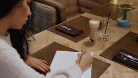 Den attraktiva brunettflickan med lockigt hår skriver en dikt i en restaurang stock video