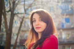 Den attraktiva brunettflickan tycker om v?rdet fria och ser tnekameran p? byggnadsbakgrund arkivfoto