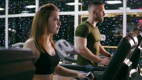 Den attraktiva caucasian flickan startar att köra på trampkvarnen i sportidrottshallen Den unga attraktiva mannen kör bakom arkivfilmer