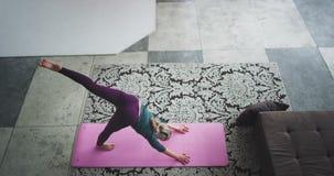 Den attraktiva damen gör yoga poserar i morgonen i den moderna vinddesignen uppifrån som fångar videoen, henne får energi stock video