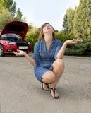 Den attraktiva desperata och förvirrade kvinnan strandade på vägrenen med bruten olycka för krasch för bilmotorfel som kallar på  Royaltyfri Foto