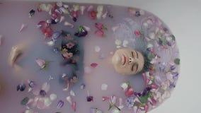 Den attraktiva flickabadningen mjölkar in badet som fylls med doftande blommor av knoppar som hon stiger ned och stiger från vatt lager videofilmer