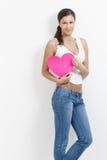 den attraktiva flickan hands hjärta rosa le Arkivbilder