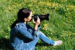 Den attraktiva flickan i en äng tar bilder av blommor Arkivfoton