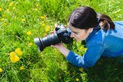 Den attraktiva flickan i en äng tar bilder av blommor Royaltyfria Bilder