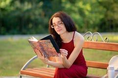 Den attraktiva flickan i Eyesglasses och lång röd klänning sitter på bänken i staden parkerar och att läsa någon bok och Royaltyfria Bilder