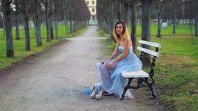 Den attraktiva flickan i silver och blåttklänning sitter på bänk i gångallén som poserar, gör framsidor och har gyckel under foto arkivfilmer
