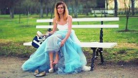 Den attraktiva flickan i silver och blåttklänning sitter på bänk i gångallén som sätter på höjdpunkten heeled skor och, talar att stock video