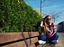 Den attraktiva flickan i solglasögon som på våren kopplar av, parkerar medan den lästa boken Arkivbilder