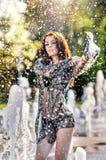 Den attraktiva flickan i svart genomskinligt skyler att spela med vatten i en varmmast dag för sommar Våt flicka som tycker om sp Royaltyfria Foton