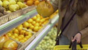 Den attraktiva flickan kommer till ställa utwitrhfrukterna och väljer apelsiner och kiwin lager videofilmer