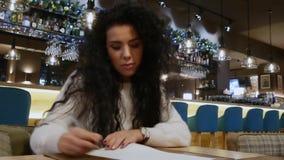 Den attraktiva flickan med lockigt hår målar en hjärta i en restaurang lager videofilmer