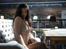 Den attraktiva flickan med lockigt hår och långa ben i en kort kjol sitter på soffan på tabellen arkivfoton