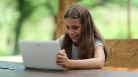 Den attraktiva flickan med minnestavladatoren sitter på tabellen i summerhouse stock video