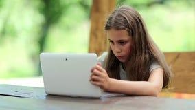 Den attraktiva flickan med minnestavladatoren sitter på tabellen i summerhouse arkivfilmer