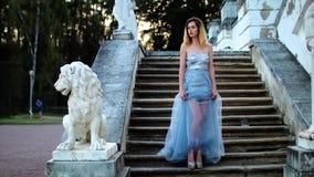 Den attraktiva flickan med svarta krön och lockigt hår i silver och blåttklänning i höjdpunkt heeled skoställningar på trappa med lager videofilmer