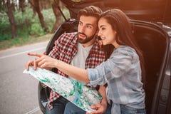 Den attraktiva flickan sitter med hennes pojkvän i stam för bil` s och att peka som är rättframt Hon ler Grabben är royaltyfria foton