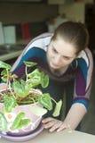 Den attraktiva flickan tar omsorg av en växt i kruka Arkivbilder