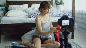 Den attraktiva gladlynta kvinnan som sitter nära den videopd bloggen för sänginspelning om handarbetebarn` s, beklär hemma stock video