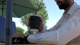 Den attraktiva grabben med ett skägg i en vit skjorta sitter på en tabell i ett gatakafé som skriver på ett bärbar datortangentbo arkivfilmer