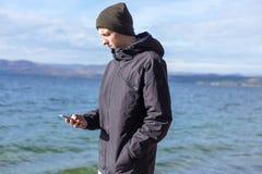 Den attraktiva grabben rymmer en smart telefon och använder den fotografering för bildbyråer
