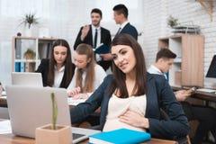Den attraktiva gravida flickan arbetar i regeringsställning med kollegor Gravid affärskvinna i workspace maternity arkivbilder