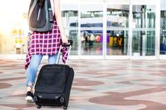 Den attraktiva härliga handelsresandekvinnan vaknar till flygplatsen och dra arkivfoton