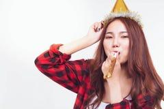 Den attraktiva härliga kvinnan som blåser partivisslingen och, bär partihatten för att fira nytt år, födelsedag, partiet eller fe arkivbilder